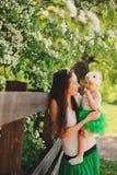 Πορτρέτο άνοιξη του παιχνιδιού κορών μητέρων και μωρών υπαίθριου στο ταίριασμα της εξάρτησης - μακριά φούστες και πουκάμισα στοκ φωτογραφία με δικαίωμα ελεύθερης χρήσης