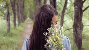 Πορτρέτο Ένα γλυκό όμορφο μικρό κορίτσι ρουθουνίζει μια ανθοδέσμη των λουλουδιών που στέκονται στη φύση μια ηλιόλουστη ημέρα χαμο απόθεμα βίντεο
