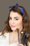 Πορτρέτο - ένα πρόσωπο του όμορφου νέου κοριτσιού με τις βούρτσες για το α Στοκ Φωτογραφία