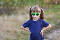 Πορτρέτο λίγου μοντέρνου κοριτσιού στα πράσινα γυαλιά ηλίου υπαίθρια Στοκ φωτογραφία με δικαίωμα ελεύθερης χρήσης