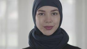 Πορτρέτο ανεξάρτητου νέου μουσουλμανικού σοβαρού βέβαιου κοιτάγματος γυναικών στη κάμερα που φορά το παραδοσιακό headscarf o απόθεμα βίντεο