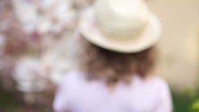 Πορτρέτο από πίσω ενός μικρού κοριτσιού σε έναν κήπο Magnolia απόθεμα βίντεο