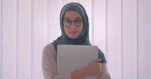 Πορτρέτο αρκετά της μουσουλμανικής επιχειρηματία στο hijab και των γυαλιών που κρατούν τα ρολόγια lap-top ήρεμα στη κάμερα απόθεμα βίντεο
