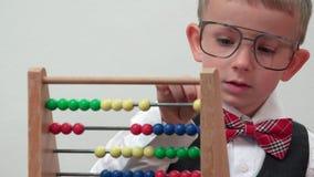 Πορτρέτο αστείο λίγου παιδιού με μεγάλα eyeglasses που αριθμεί, ξύλινος υπολογισμός απόθεμα βίντεο