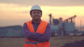 Πορτρέτο βραδιού ενός ευτυχούς μηχανικού στο υπόβαθρο των εγκαταστάσεων Μέσης ηλικίας άτομο της ασιατικής εμφάνισης φιλμ μικρού μήκους