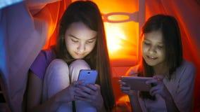 Πορτρέτο δύο έφηβη που δακτυλογραφούν το μήνυμα στα κοινωνικά μέσα στα κινητά τηλέφωνα στην κρεβατοκάμαρα τη νύχτα Στοκ Εικόνες