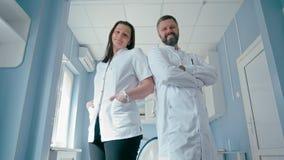 Πορτρέτο δύο βέβαιων γιατρών στο νοσοκομείο που κοιτάζει στη κάμερα φιλμ μικρού μήκους