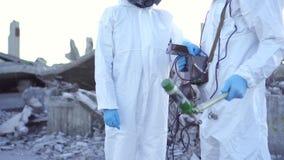 Πορτρέτο δύο επιστήμονες στα προστατευτικές κοστούμια και τις μάσκες και ένας επόπτης ακτινοβολίας, ακτινοβολία μέτρου περιπάτων απόθεμα βίντεο