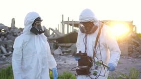 Πορτρέτο δύο επιστημόνων στις άσπρες φόρμες και τις προστατευτικές μάσκες που παίρνουν τις μετρήσεις της ακτινοβολίας στο ηλιοβασ απόθεμα βίντεο