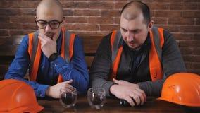 Πορτρέτο δύο εργαζομένων που φορούν hardhats που παίρνουν ένα σπάσιμο από τον καφέ κατανάλωσης εργασίας και στήριξη στο γραφείο κ απόθεμα βίντεο
