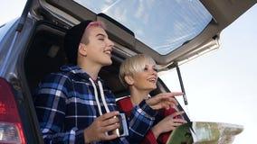 Πορτρέτο δύο κοριτσιών hipsters που κάθονται στον κορμό του τσαγιού κατανάλωσης αυτοκινήτων εξετάζοντας την παραγωγή οδικών χαρτώ απόθεμα βίντεο