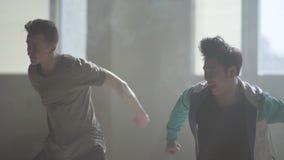 Πορτρέτο δύο τύπων που χορεύουν μπροστά από το μεγάλο παράθυρο στο σκοτάδι στο εγκαταλειμμένο κτήριο Έφηβοι που κάνουν την κίνηση φιλμ μικρού μήκους