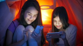 Πορτρέτο δύο χαμογελώντας κοριτσιών που δακτυλογραφούν τα μηνύματα στα κινητά pnones τη νύχτα Στοκ Εικόνες