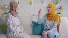 Πορτρέτο δύο χαμογελώντας όμορφες κωφές νέες μουσουλμανικές γυναίκες στα hijabs που μιλούν με τη γλώσσα σημαδιών στο καθιστικό φιλμ μικρού μήκους