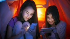 Πορτρέτο δύο χαριτωμένων κοριτσιών στις πυτζάμες με τα κινητά τηλέφωνα τη νύχτα Στοκ Φωτογραφία