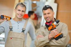 Πορτρέτο δύο όμορφοι εργάτες που κρατούν τα εργαλεία στοκ εικόνα με δικαίωμα ελεύθερης χρήσης