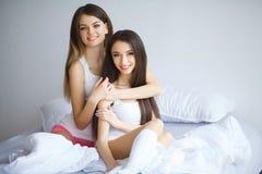 Πορτρέτο δύο όμορφων εύθυμων κοριτσιών με την ακτινοβολία του αγκαλιάσματος χαμόγελων στοκ εικόνα