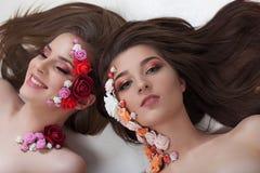 Πορτρέτο δύο όμορφων κοριτσιών με τα λουλούδια applique στο πρόσωπο Στοκ Εικόνες