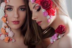 Πορτρέτο δύο όμορφων κοριτσιών με τα λουλούδια applique στο πρόσωπο Στοκ φωτογραφία με δικαίωμα ελεύθερης χρήσης