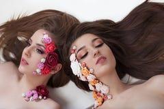 Πορτρέτο δύο όμορφων κοριτσιών με τα λουλούδια applique στο πρόσωπο Στοκ εικόνα με δικαίωμα ελεύθερης χρήσης