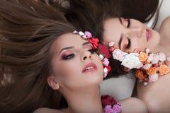 Πορτρέτο δύο όμορφων κοριτσιών με τα λουλούδια applique στο πρόσωπο Στοκ Εικόνα