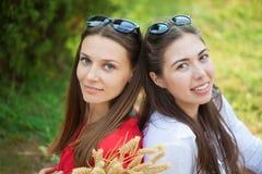 Πορτρέτο δύο όμορφων κοριτσιών σε ένα πάρκο σε ένα διάστημα αντιγράφων πικ-νίκ στοκ εικόνες