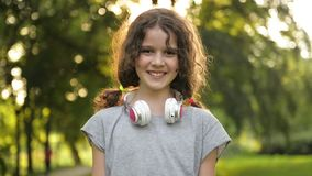 Πορτρέτο ελκυστικού καυκάσιου λίγο κορίτσι σπουδαστών με τα όμορφα καφετιά μάτια με τα ακουστικά Ευτυχές χαμογελώντας παιδί απόθεμα βίντεο