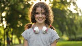 Πορτρέτο ελκυστικού καυκάσιου λίγο κορίτσι σπουδαστών με τα όμορφα καφετιά μάτια με τα ακουστικά Ευτυχές χαμογελώντας παιδί φιλμ μικρού μήκους