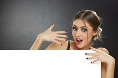 Έκπληκτο νέο κορίτσι που κρατά τον κενό πίνακα διαφημίσεων Στοκ Φωτογραφία