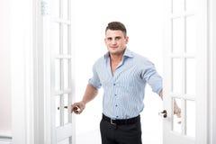 Πορτρέτο ενός έξυπνου σοβαρού προκλητικού νεαρού άνδρα που στέκεται στο εγχώριο εσωτερικό πορτών στοκ εικόνα