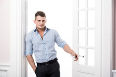 Πορτρέτο ενός έξυπνου σοβαρού προκλητικού νεαρού άνδρα που στέκεται στο εγχώριο εσωτερικό πορτών στοκ εικόνα με δικαίωμα ελεύθερης χρήσης