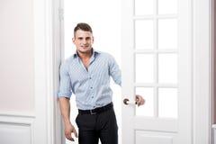 Πορτρέτο ενός έξυπνου σοβαρού προκλητικού νεαρού άνδρα που στέκεται στο εγχώριο εσωτερικό πορτών στοκ φωτογραφία