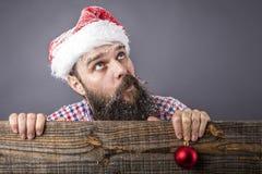 Πορτρέτο ενός αστείου γενειοφόρου ατόμου με το santa ΚΑΠ που κρατά ένα κόκκινο rou Στοκ Φωτογραφία