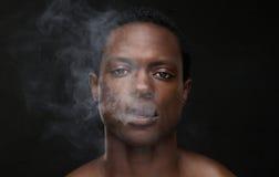 Άτομο αφροαμερικάνων με το στόμα καπνού που βγαίνει στοκ φωτογραφίες