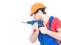 Ένα άτομο που τρυπά μια τρύπα στον τοίχο με τρυπάνι. Στοκ εικόνες με δικαίωμα ελεύθερης χρήσης