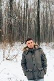 Πορτρέτο ενός ατόμου σε ένα χειμερινό δάσος και ένα θερμό σακάκι στοκ εικόνα με δικαίωμα ελεύθερης χρήσης