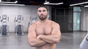 Πορτρέτο ενός βάναυσου νεαρού άνδρα με έναν γυμνό κορμό στη γυμναστική φιλμ μικρού μήκους