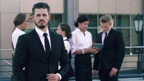 Πορτρέτο ενός βέβαιου επιχειρησιακού ατόμου που στέκεται μπροστά από τους συναδέλφους του απόθεμα βίντεο