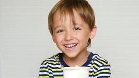Πορτρέτο ενός γελώντας αγοριού Ευτυχές μικρό παιδί που τρώει το γιαούρτι καθμένος στον πίνακα και εξετάζοντας τη κάμερα απόθεμα βίντεο