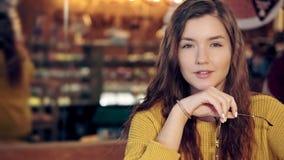 Πορτρέτο ενός γοητευτικού κοριτσιού σε μια άνετη καφετερία με τα γυαλιά φιλμ μικρού μήκους