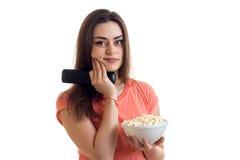 Πορτρέτο ενός γοητευτικού νέου κοριτσιού με τον τηλεχειρισμό από τη TV και pop-corn υπό εξέταση Στοκ Εικόνες