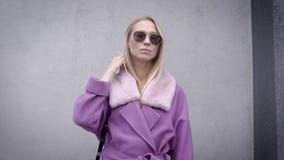 Πορτρέτο ενός γοητευτικού ξανθού κοριτσιού σε ένα πορφυρό παλτό και τα γυαλιά ηλίου, κρύος καιρός πτώσης απόθεμα βίντεο
