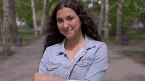 Πορτρέτο ενός ελκυστικού νέου κοριτσιού με μακρυμάλλη Το όμορφο κορίτσι στέκεται στην οδό απόθεμα βίντεο