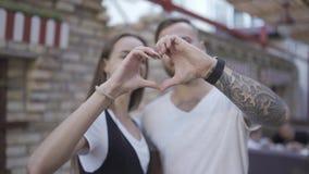 Πορτρέτο ενός ελκυστικού νέου europian ζεύγους που γελά και που κάνει μια μορφή καρδιών με τα χέρια τους σε σε αργή κίνηση απόθεμα βίντεο