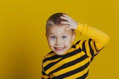 Πορτρέτο ενός ελκυστικού στοχαστικού αγοριού σε ένα ριγωτό πουλόβερ που κρατά ένα χέρι στο κεφάλι του σε ένα κίτρινο υπόβαθρο στοκ εικόνα με δικαίωμα ελεύθερης χρήσης