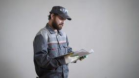 Πορτρέτο ενός ενήλικου ατόμου στα γάντια, μια εκμετάλλευση οικοδόμων στα σχέδια χεριών του για την επισκευή ενός διαμερίσματος απόθεμα βίντεο