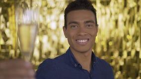 Πορτρέτο ενός εξωτικού ατόμου σε ένα χρυσό υπόβαθρο το άτομο χαμογελά και άντεξε μια δεξαμενή της σαμπάνιας 4K φιλμ μικρού μήκους