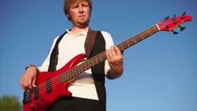 Πορτρέτο ενός επαγγελματικού μουσικού που παίζει τη μουσική, ίσως βράχος, στη βαθιά κιθάρα απόθεμα βίντεο