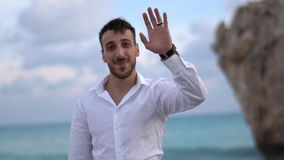 Πορτρέτο ενός επιτυχούς ατόμου σε ένα άσπρο πουκάμισο που κυματίζει ένα χέρι Όμορφες στάσεις τύπων χαμόγελου στην ακτή E r απόθεμα βίντεο