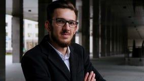 Πορτρέτο ενός επιτυχούς επιχειρηματία σε ένα κλασικό κοστούμι Με τα γυαλιά και εξετάζει τη κάμερα και το χαμόγελο Με διασχισμένος φιλμ μικρού μήκους